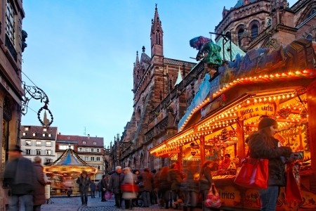 alsace: Strasbourg,France- December 12, 2012: Image of people walking among festive street stands and merry-go-round in Broglie Square near the Cathedral in Strasbourg during the Christmas Market.In Strasbourg there are 12 Christmas Markets which make this city a