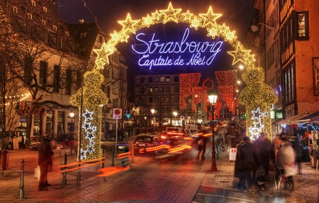 alsace: Strasbourg,France- December 12, 2012: People and cars passing under the beautifully illuminated and decorated entrance in the old part of Strasbourg city during the winter holidays. During December in Strasbourg are 12 Christmas Markets which make this ci