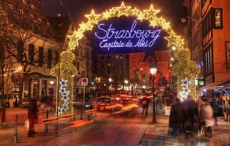 Strasbourg, France-12. Dezember 2012: Menschen und vorbeifahrende Autos unter dem wunderschön beleuchtet und dekoriert Eingang in den alten Teil der Stadt Straßburg während der Winterferien. Im Dezember in Straßburg sind 12 Weihnachtsmärkte, die dieses ci machen
