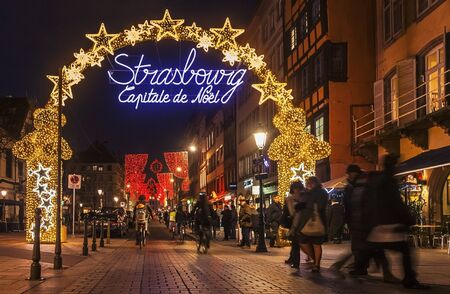 Strasbourg,France- December 12, 2012: People walking and riding bicycles under the beautifully illuminated and decorated entrance in the old part of Strasbourg city during the winter holidays. During December in Strasbourg are 12 Christmas Markets which m