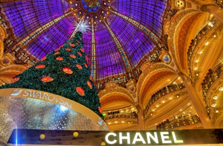 lafayette: Paris,France- December 18, 2012: Upper part of the Chanel stand and the beautiful decorated Christmas tree in Galleries Lafayette in Paris.This is a very foamous upmarket French department store opened for the first time in the center of the big city in 1