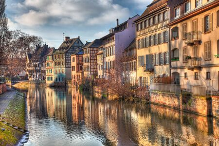 waterway: Beautiful reflections at the sunset of traditional buildings in a water canal in Strasbourg in eastern France.