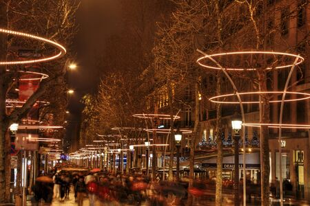 walk of fame: Paris,France- December 31, 2012: Crowd of people walking in a rainy New Years Eve night on the Avenue des Champs Elysees in Paris few hours before the end of the year 2012.Due to very bad weather condition (heavy rain) there was not the usual fireworks s