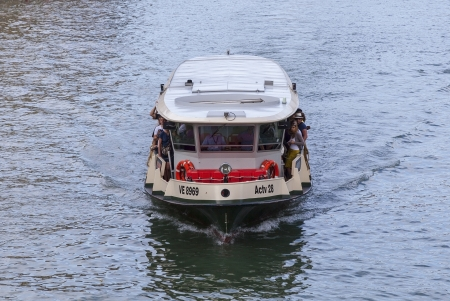 ply: Venice, Italy- July 28,2011:  Image of Il Vaporeto with tourists sailing on the Grand Canal in Venice. Il Vaporeto is a motorised waterbus which ply regular routes along the major canals and between the citys islands.