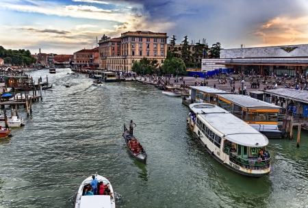 waterbus: Venice, Italy- July 28,2011:  Image of a traditional gondolier and a waterbus on the Grand Canal in Venice near the Venetian railway station and Ferrovia Vaporetto station. Editorial
