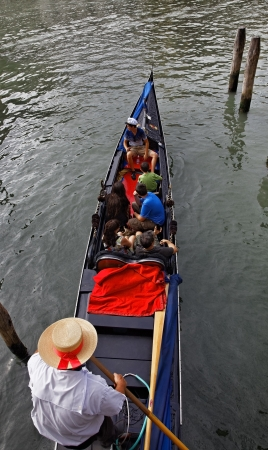 Venice, Italy- July 28,2011: Bird eye view of a gondolier in his gondola full of tourists on the Grand Canal in Venice. Stock Photo - 17228570