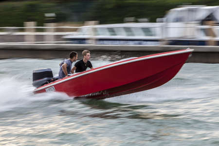 speed boat: Venice, Italy- July 30,2011: Two young men cruising the waters near Venice in a red high speed boat.