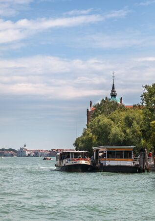 waterbus: Venice, Italy- July 28,2011:  Image of a specific waterbus (vaporetto) with tourists stoping in the Sacca Fisola station on a canal in Venice. Vaporeto is a motorised waterbus which ply regular routes along the major canals and between the citys islands.