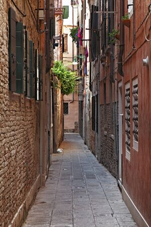 Image of a typical narrow street between walls of houses in Venice. Stock Photo - 17239342