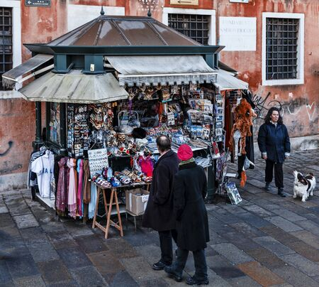 Venice,Italy- February 12, 2012: People passing by a kiosk full of various souvenirs on a small street in Venice Stock Photo - 17355974