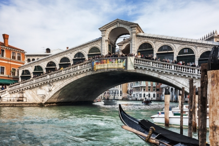 Venice,Italy- February 18, 2012: Image of The Rialto Bridge,the oldest bridge accross the Grand Canal in Venice, full of people admiring a beautiful panorama during the Carnival days.
