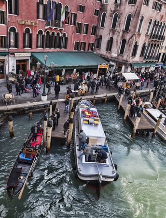 Venice, Italy-February 18, 2012: Image of tourists walking near a dock with a gondola and a transporter ship in the Rialto Bridge area in Venice.