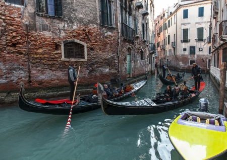 gondoliers: Venice,Italy- February 18, 2012:Three gondolas full of tourists cruise on a narrow canal between buildings in Venice, durign the Carnival days. Editorial