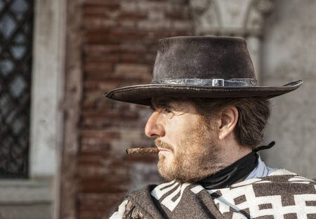 Venice, Italy-February 18, 2012:Environmental portrait of a person with a six-shooter disguised as an old time western mercenary posing for tourists in Venice during The Carnival days. Stock Photo - 17403448
