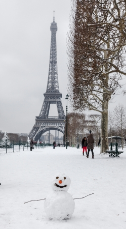 paris night: Paris,France- January 19, 2013: Winter image with a funny snowman and people on Champs de Mars after the first night snowfall of the year in Paris.