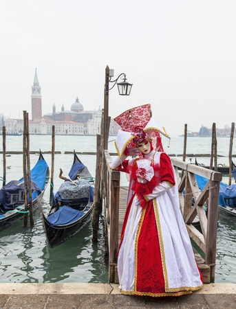 Venice, Italy- February 18th, 2012: Image of a person in a beautiful red and white costume, posing in San Marco Square  in Venice during the Canival days. Stock Photo - 17403447
