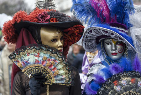 Venice, Italy- February 18th, 2012: Environmental portrait of two persons wearing nice colorful costumes and masks during the Venice Carnival. Stock Photo - 17523280
