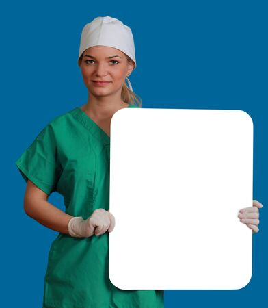 A young woman doctor holding an empty white bill board against a blue background. photo