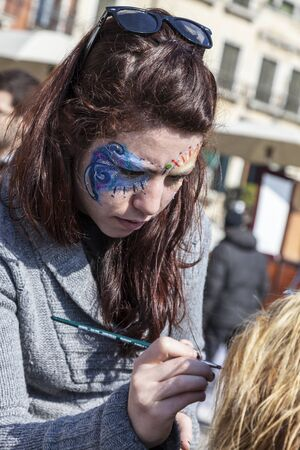 sestiere: Venice,Italy-February 26, 2011: Environmental portrait of a female street face painter working on Sestiere Castello in Venice during the Venice carnival days.