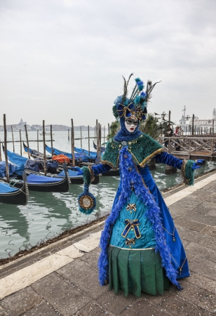 venetian: Venice, Italy- February 18th, 2012: A person disguised in a beautiful blue disguise holding a mirror pose in San Marco Square in front of the gondolas port in Venice, during The Carnival days.