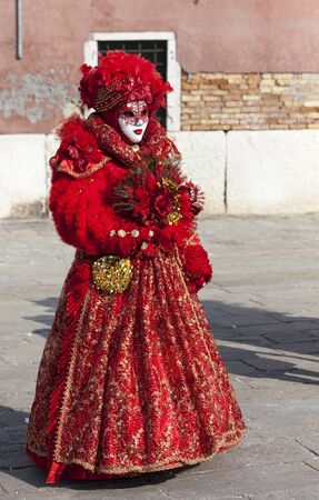 sestiere: Venice, Italy- February 18th, 2012: Image of a person in a beautiful red Venetian costume posing in Sestiere Castello during The Venice Carnival days. Editorial