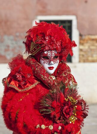 Venice, Italy- February 18th, 2012:Environmental portrait of a person in a beautiful red Venetian costume posing in Sestiere Castello during The Venice Carnival days. Stock Photo - 17914333