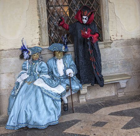 specific: Venice, Italy- February 19th, 2012: Image of three persons disguised in specific costumes posing near the Doges Palace during the Venice Carnival days.