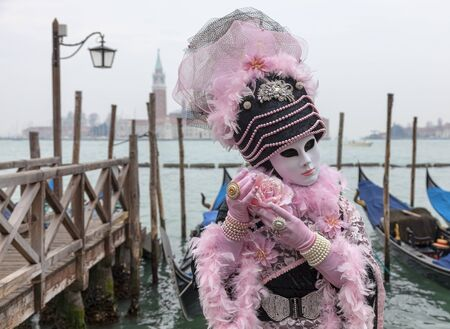 venice mask: Venice, Italy- February 19th, 2012: Portrait of a person in a traditional mask posing with a rose near the gondolas dock in San Marco Square during the Venice Carnival days. Editorial