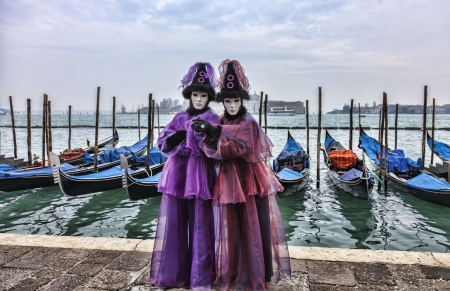 Venice, Italy- February 198th, 2012:A couple disguised in Venetian costumes pose in front of gondolas dock during the Venice Carnival days.