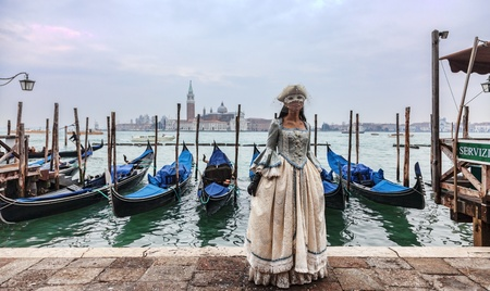 Venice, Italy- February 198th, 2012:A woman ina beautiful dress and colombina mask posing in front of gondolas dock during the Venice Carnival.