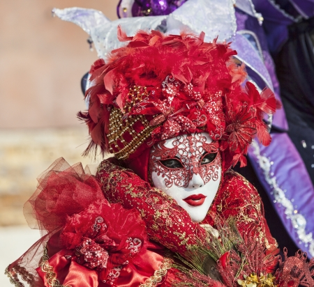 venice carnival: Venice, Italy- February 18th, 2012:Environmental portrait of a person in a beautiful red Venetian costume posing in Sestiere Castello during The Venice Carnival days. Editorial
