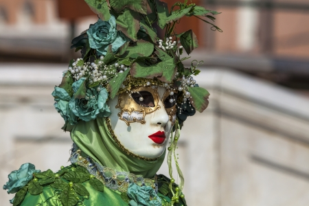 sestiere: Venice, Italy- February 18th, 2012:Environmental portrait of a person in sophisticated green Venetian costume posing in Sestiere Castello during The Venice Carnival days.