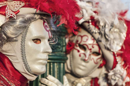 Venice, Italy- February 18th, 2012: Environmental portrait of two persons wearing nice colorful costumes and masks during the Venice Carnival.