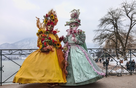 Annecy, France, February 23, 2013: Couple disguised in beautiful costumes posing on the Lovers Bridge over a canal canal in Annecy, France,  during a Venetian Carnival.