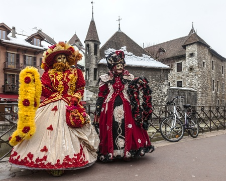 Annecy, France, February 23, 2013: Two unidentified disguised persons posing in Annecy near a water canal in front of traditional buildings during a Venetian Carnival which celebrates the beauty of real Venice.