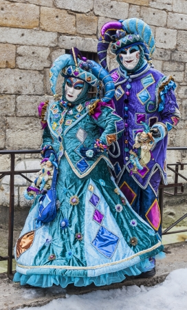 Annecy, France, February 23, 2013: Unidentified couple disguised in blue jesters costumes pose in front of a traditional stone wall in Annecy during a Venetian Carnival, which celebrates the beauty of the real Venice.