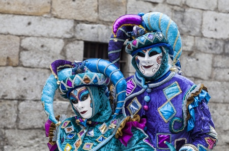 disguised: Annecy, France, February 23, 2013: Portrait of an Unidentified couple disguised in blue jesters costumes pose in front of a traditional stone wall in Annecy during a Venetian Carnival, which celebrates the beauty of the real Venice.