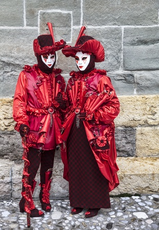 Annecy, France, February 23, 2013: Couple disguised in beautiful red costumes posing in front of a stone walll in Annecy, France,  during a Venetian Carnival.