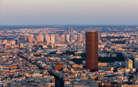 highrises: Aerial view of Paris in a late spring afternoon with Montaparnasse Tower and highrises district La Grenelle in the distance.