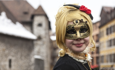 disguised: Annecy, France, February 23, 2013: Environmental portrait of a girl in Colombina mask posing in front of The Palais de lIsle in Annecy during a Venetian Carnival which celebrates the beauty of the real Venice. Editorial