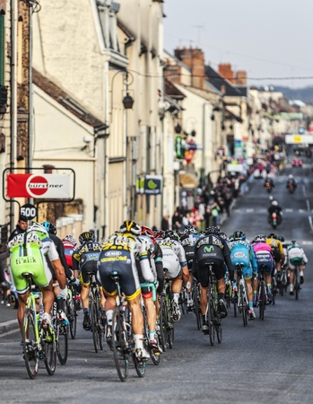 peloton: Nemours,France- March 4, 2013: Image of the peloton riding fastly in a narrow road in Nemours, during the first stage of the famous road bicycle race Paris-Nice, on March 4, 2013. Editorial