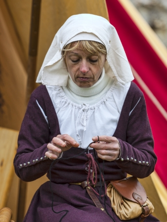 skillful: Nogent le Rotrou,France-May 19,2012: Environmental portrait of a medieval woman habdworking with some threads in front of her tent during a reenactment festival in Nogent le Rotrou in France.