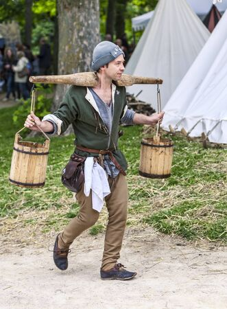 Nogent le Rotrou, France- May 19, 2012: A water-carrier walking with full water-carts on his shoulder betweeb tents during a historical reenactment festival in Nogent le Rotrou, France.