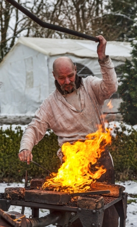 sain: Rodemack,France- December 09, 2012:Environmental portrait of a medieval blacksmith working on fire during a reenactment historical festival in Rodemack in France.
