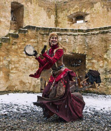 pandero: Rodemack, Francia-December 09, 2012: Una actriz disfrazada de un derrumbe mujer está bailando afuera, cerca de las murallas de la fortaleza, mientras caía aguanieve, durante un festival de recreación histórica en Rodemack, Francia. Editorial