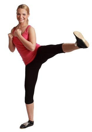 female kick: Young blonde woman kickboxing against a white background.