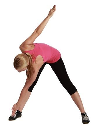 jambes �cart�es: Blond femme debout avec les jambes �cart�es se penchant avec une main touchant un pied et l'autre ressuscit�, sur un fond blanc. Banque d'images