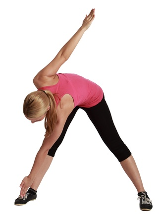 flexable: Blond woman standing with legs apart bending down with one hand touching one foot and the other raised up, against a white background. Stock Photo