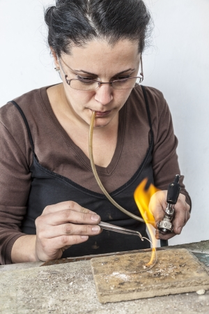 jeweller: Portrait of a female jeweler working with a flame on a piece of silver wire.