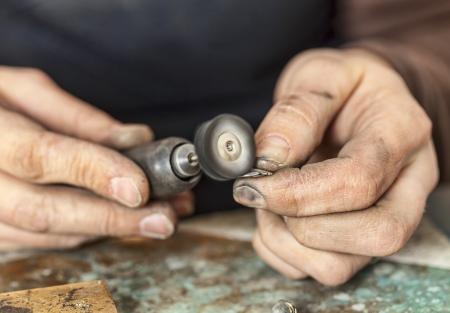 trabajo manual: Primer plano de las manos de un joyero pulir una pieza de plata. Foto de archivo